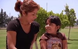 Mujer y niña mirándose a los ojos y sonriendo