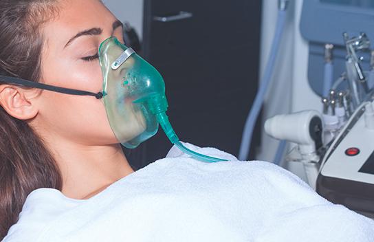 Fotografía de mujer con los ojos cerrados. Trae puesta una bata hospitalaria y tiene colocado un nebulizador