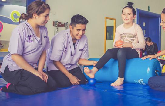 Una niña es atendida por un grupo de terapeutas en un Centro Teletón