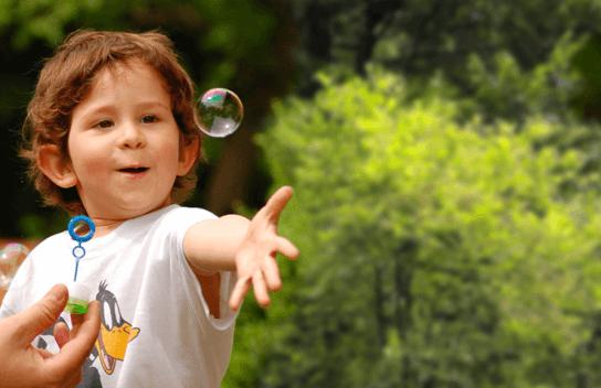 Imagen de niño que sonríe al jugar con una burbuja de jabón
