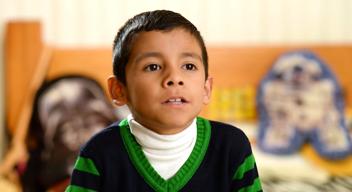 Niño con suéter azul marino y franjas verdes