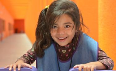Niña con uniforme del CAT juega sobre pieza de rompecabezas gigante en un pasillo del Centro Teletón