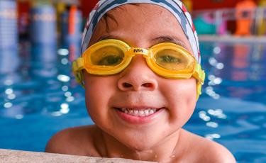 Niño con goggles sonríe a la cámara desde alberca de hidroterapia