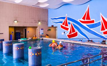 Niño recibe terapia en alberca de hidroterapia, la pared al fondo está decorada con barcos rojos