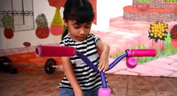 Niña jugando con su triciclo