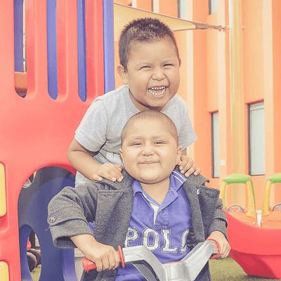 Dos niños jugando y sonriendo a la cámara