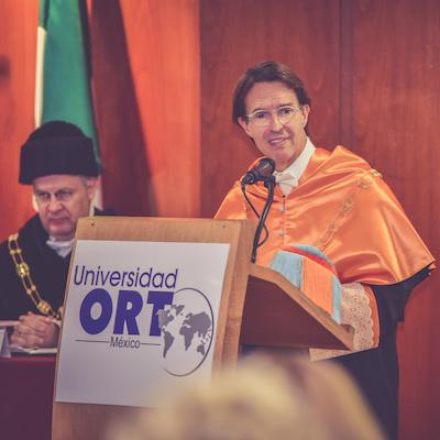 Fernando Landeros da un discurso de agradecimiento en un podio que lee: