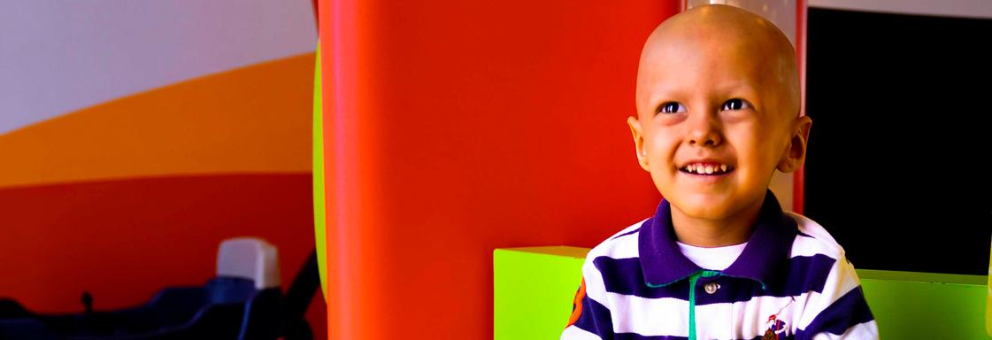Niño sin cabello sonríe mirando al cielo en los pasillos del HITO