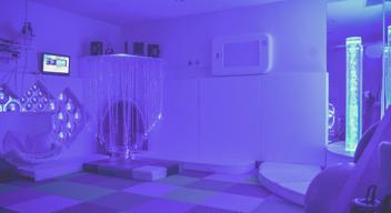 Fotografía de un Cuarto de Estimulación Multisensorial, con iluminación púrpura