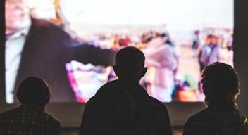 Tres personas en la oscuridad miran a una pantalla iluminada. Foto por Aneta Pawlik para Unsplash.