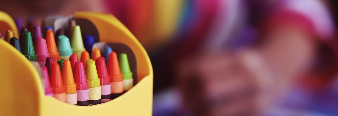 Foto de una caja de crayolas en primer plano, al fondo se ve la imagen borrosa de un niño dibujando