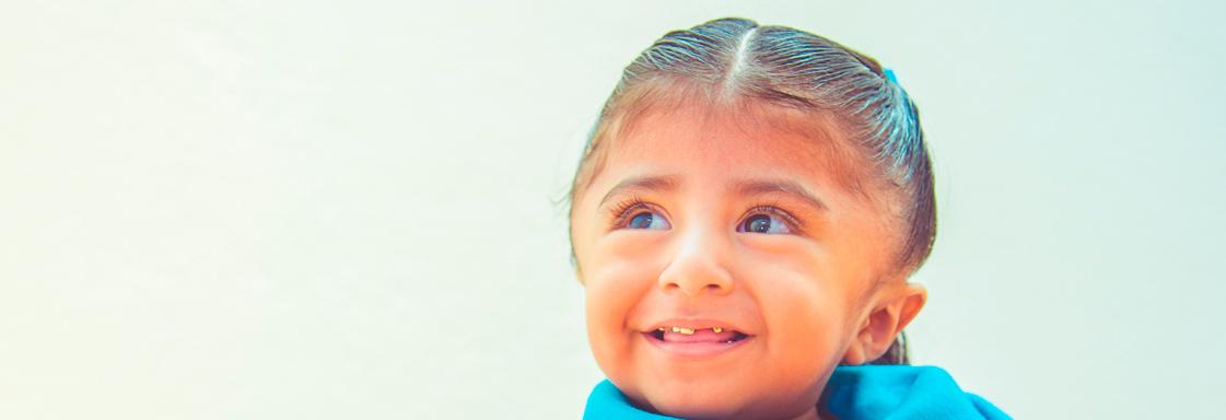 Niña con blusa azul sonríe mirando al horizonte