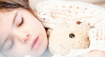 Niña dormida abraza a un oso de peluche