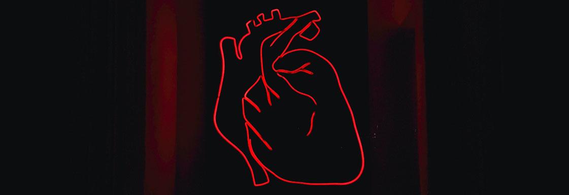 Ilustración del contorno de un corazón, con color rojo, sobre un fondo negro