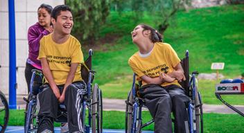 Dos usuarios de silla de ruedas platican y ríen en una cancha de baloncesto