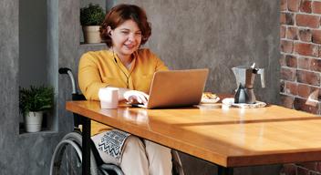 Fotografía de mujer, usuaria de silla de ruedas, sentada frente a un escritorio, con una computadora portátil y una taza de café