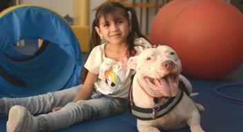 Fotografía de niña sonriendo junto a un perro blanco, sobre tapete de rehabilitación