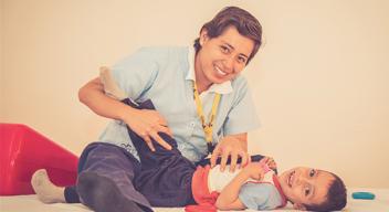 Imagen de niño con su terapeuta físico. La terapeuta está realizando estiramientos en la pierna del niño.