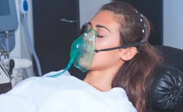 Fotografía de mujer con respirador y los ojos cerrados durante terapia respiratoria.