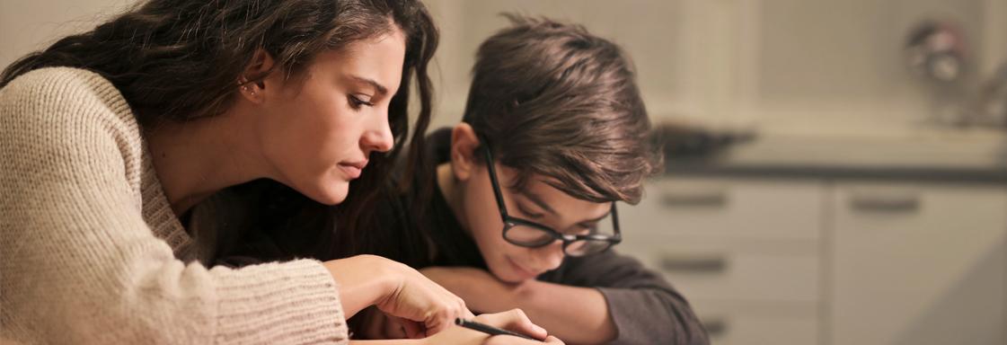 Fotografía de dos jóvenes, un hombre y una mujer, haciendo tarea en una misma libreta.