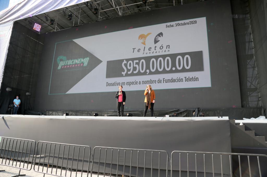 Foto de Fernando Landeros y Pamela Hamui, durante la función y el anuncio del donativo en el Autocinema Santa Fé