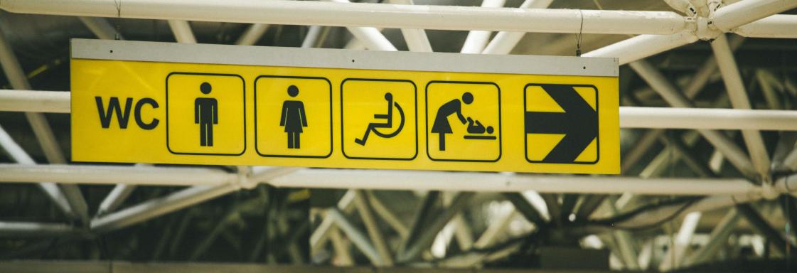 Imagen de señalización en un espacio público. De izquierda a derecha: WC, icono de hombre, icono de mujer, icono de persona usuaria de silla de ruedas, icono de cambiador de pañales, icono de una flecha señalando a la derecha. Foto por Paul Green para Unsplash