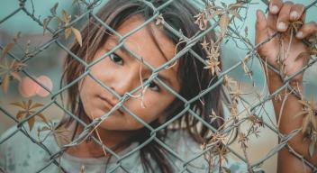 Niña en situación de pobreza mira a la cámara detrás de una reja de alambre. Foto por namo deet para Pexels