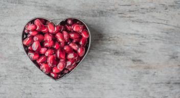 Fotografía de un plato con forma de corazón, lleno de granos de granada, sobre una mesa gris. Foto por Jessica Lewis para Pexels