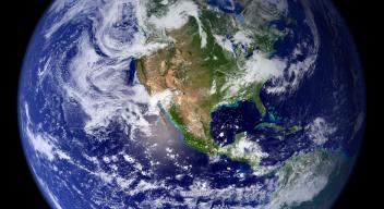 Imagen del planeta tierra sobre fondo negro, al centro está México