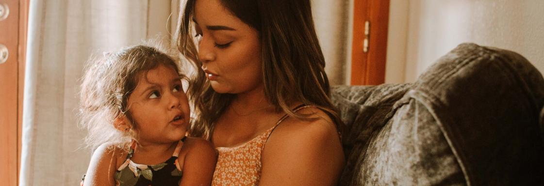 Fotografía de madre e hija. La niña tiene alrededor de 5 años. Está sentada en las piernas de su madre. Ambas están platicando.