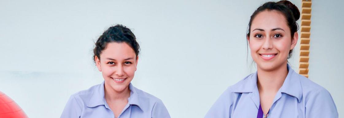 Dos alumnas, con el uniforme color púrpura de la Universidad Teletón, sonríen a la cámara en un espacio abierto con fondo blanco