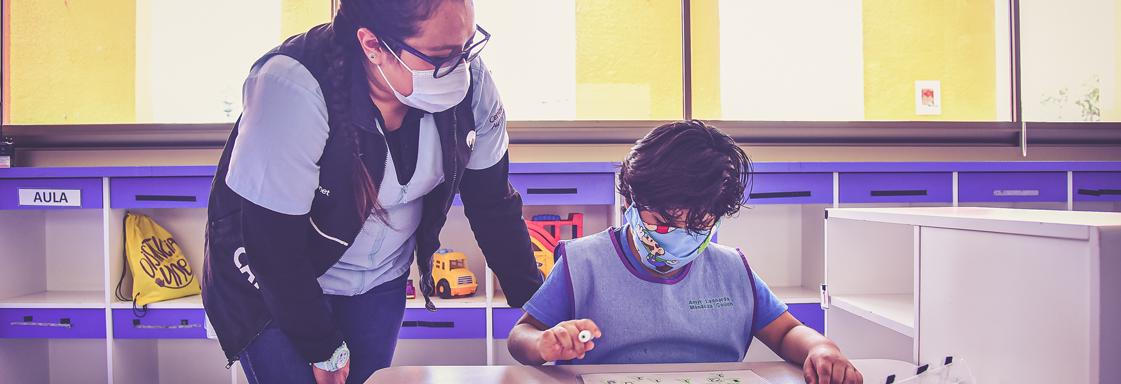 Fotografía de un niño frente a un pupitre de un salón de clases. Junto a él está una terapeuta. Se encuentran en el Centro Autismo Teletón.