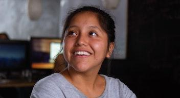 Una niña morena, de pelo negro y ojos cafés, de  alrededor 10 años, sonríe mirando hacia la izquierda.